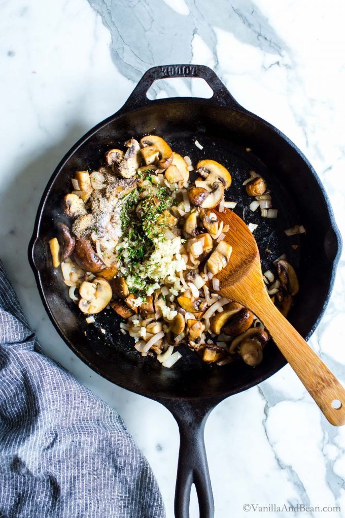 Mushroom and onion sauté in a skillet, with added garlic and herbs.