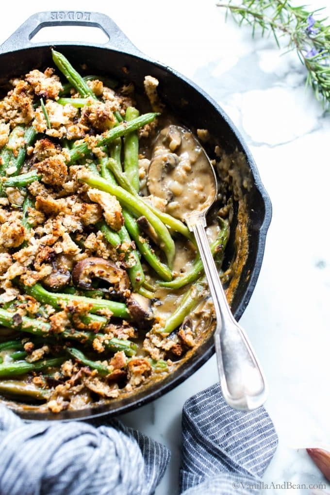 Closeup of Vegetarian Green Bean Casserole in a skillet with a serving spoon.