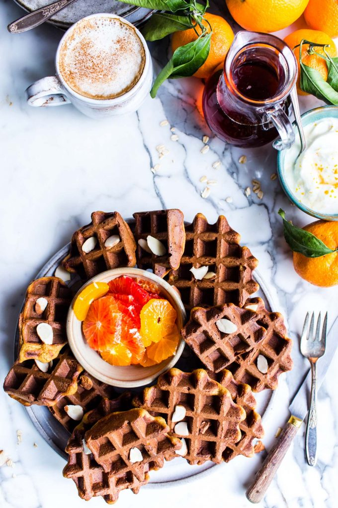 Overhead shot of Almond Orange Oat Waffles with a bowl of orange slices for topping.