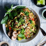 Vegetable Stir Fried Rice in a large serving bowl with lime and sesame seeds on the side.