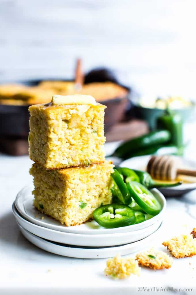 Jalapeño Cheddar Cornbread slices stacked on top of each other, on a plate with melting butter on top.