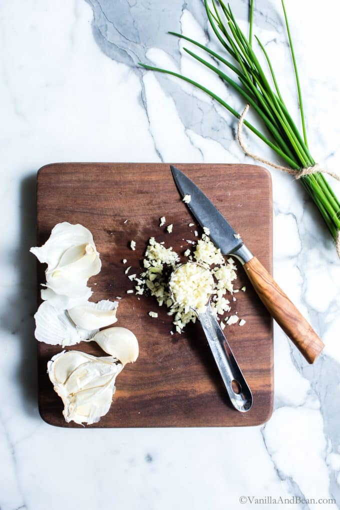 Chopping garlic on a cutting board with packed garlic in a measuring spoon.