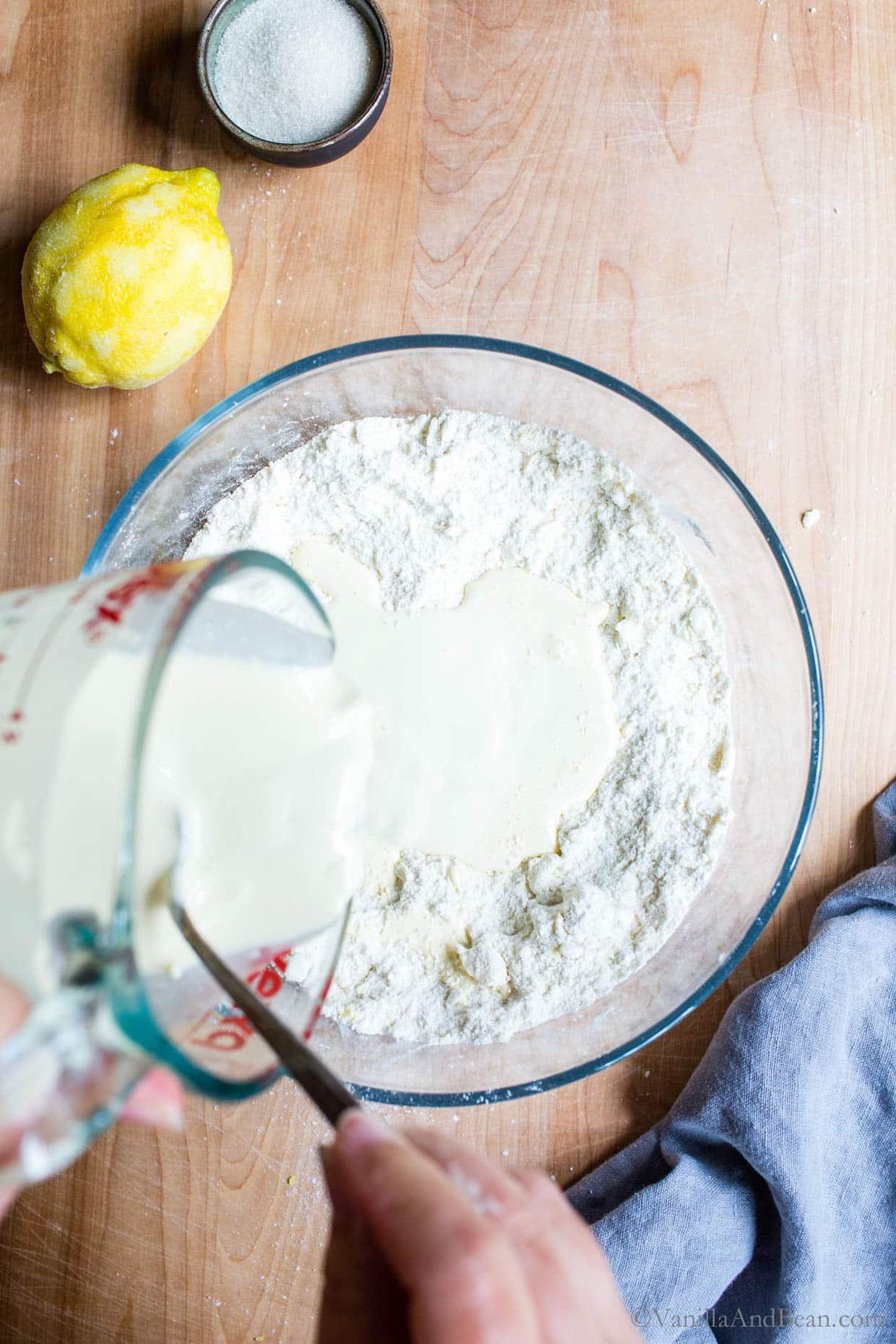 Adding a mix of cream and sourdough into the flour.
