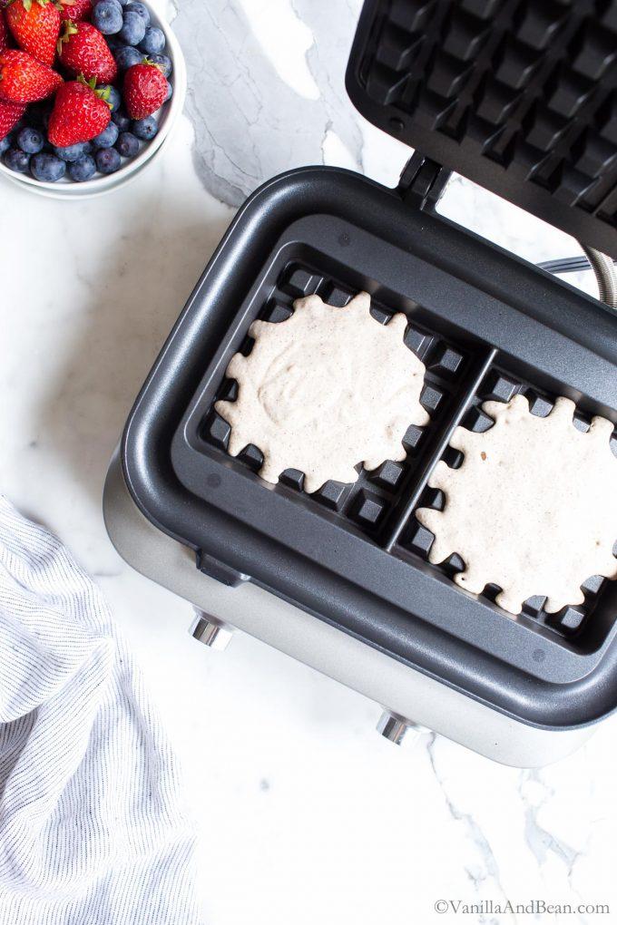 Sourdough waffles baking in a waffle iron.
