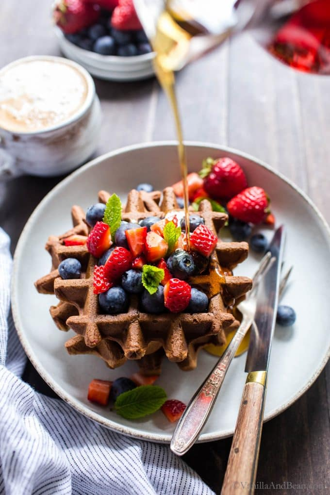 Gluten Free Sourdough Waffles on a plate topped with berries and syrup being poured over the top.