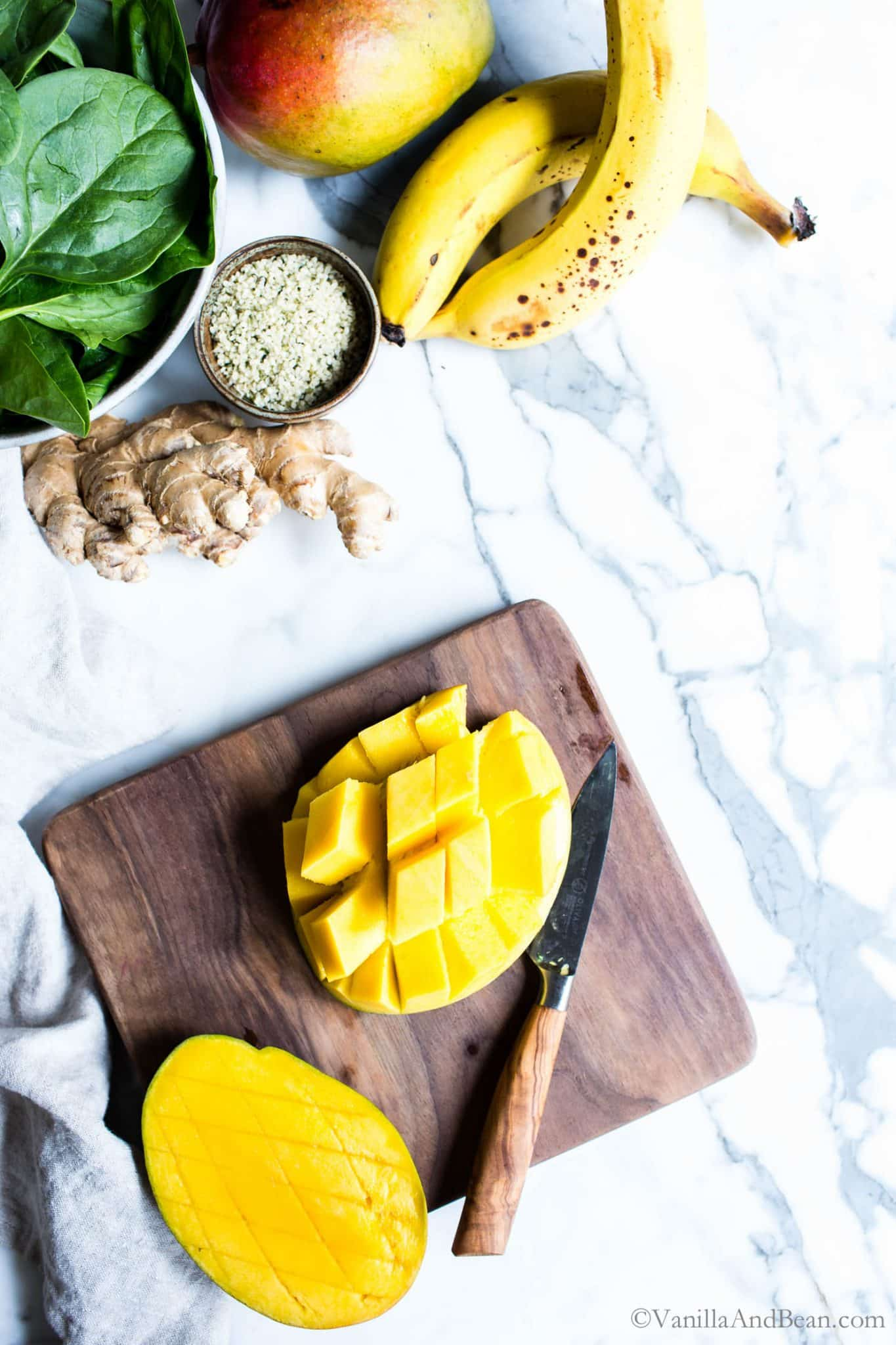 Cutting a mango on a cutting board for Mango Banana Spinach Smoothie.