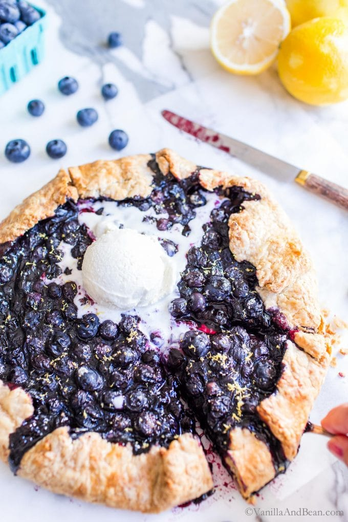 Blueberry Galette with ice cream melting in the center. One slice being pulled from the side.