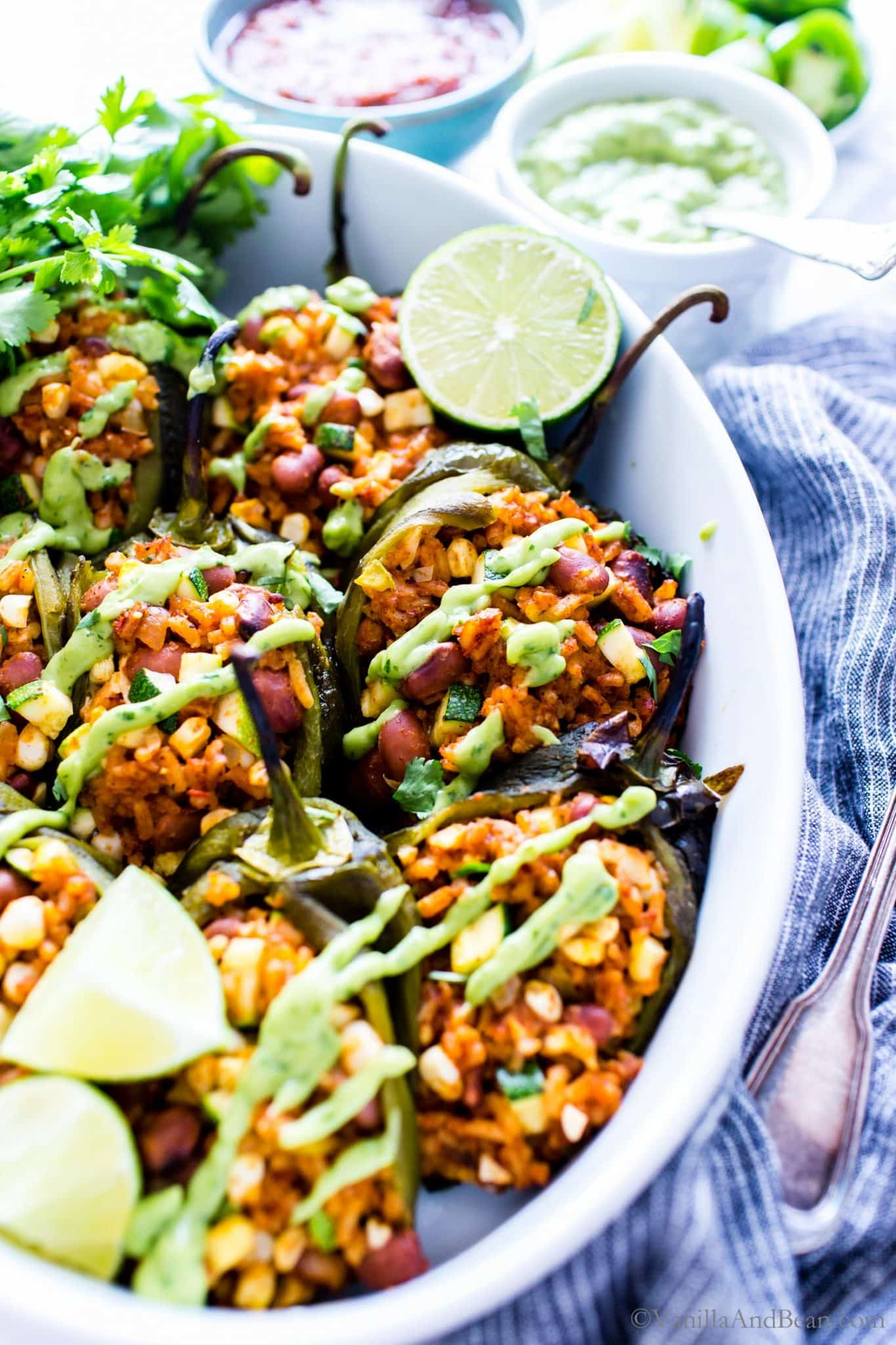 Stuffed Poblano Peppers in a roasting dish with avocado cream drizzled over the top.