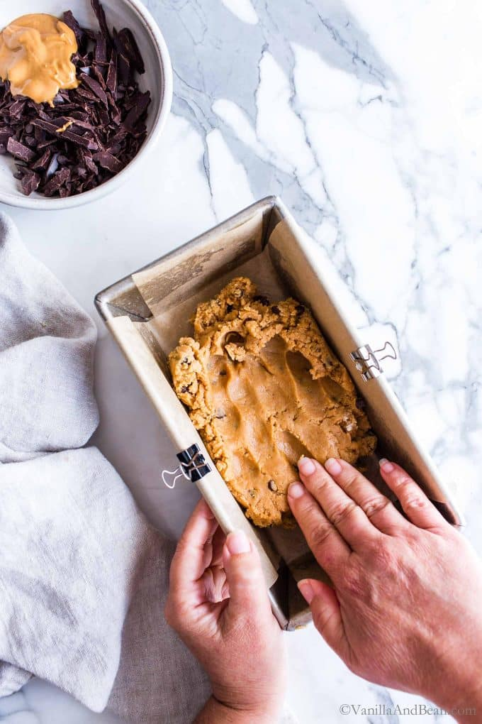 Pressing the Peanut Butter Cookie Dough into a pan for the no bake peanut butter chocolate bars.