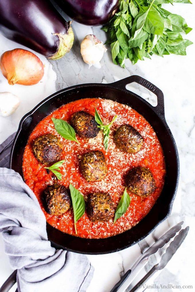 Eggplant Balls Vegan in a a pan with marinara sauce.
