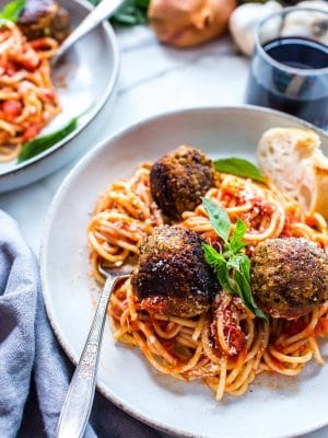 Vegan Eggplant Meatballs on spaghetti with basil.
