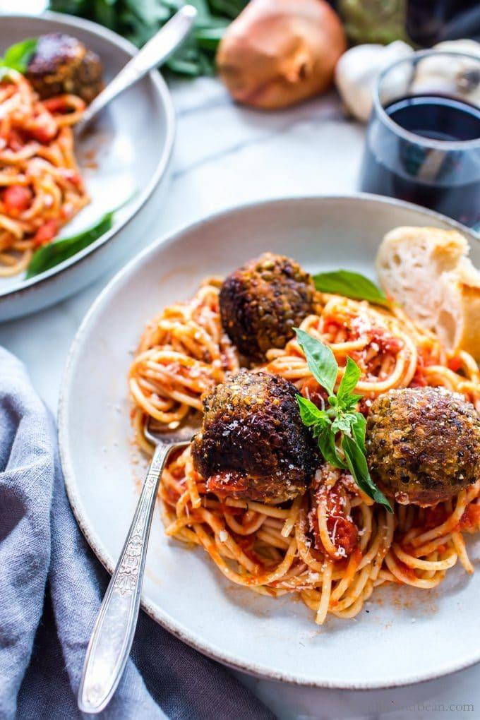 Vegan Eggplant Meatballs on spaghetti with basil.