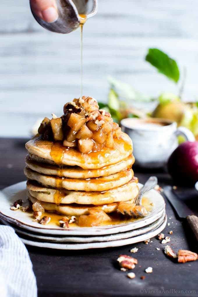A stack of oat pancakes on a plate topped with stewed apples.
