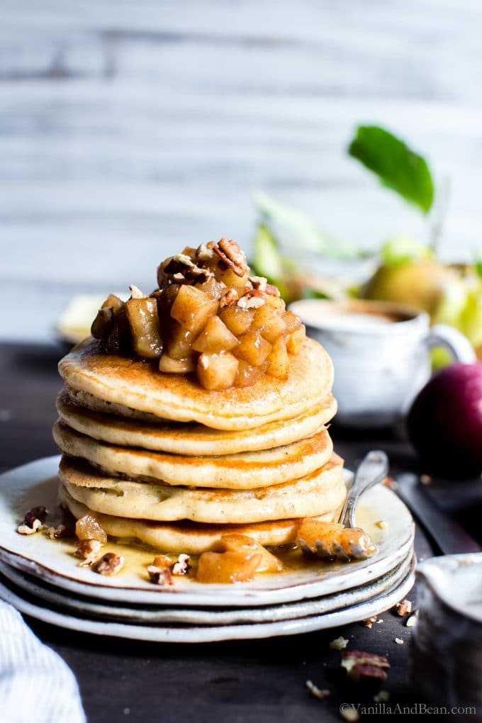A stack of overnight sourdough pancakes on a plate with apples piled on top.