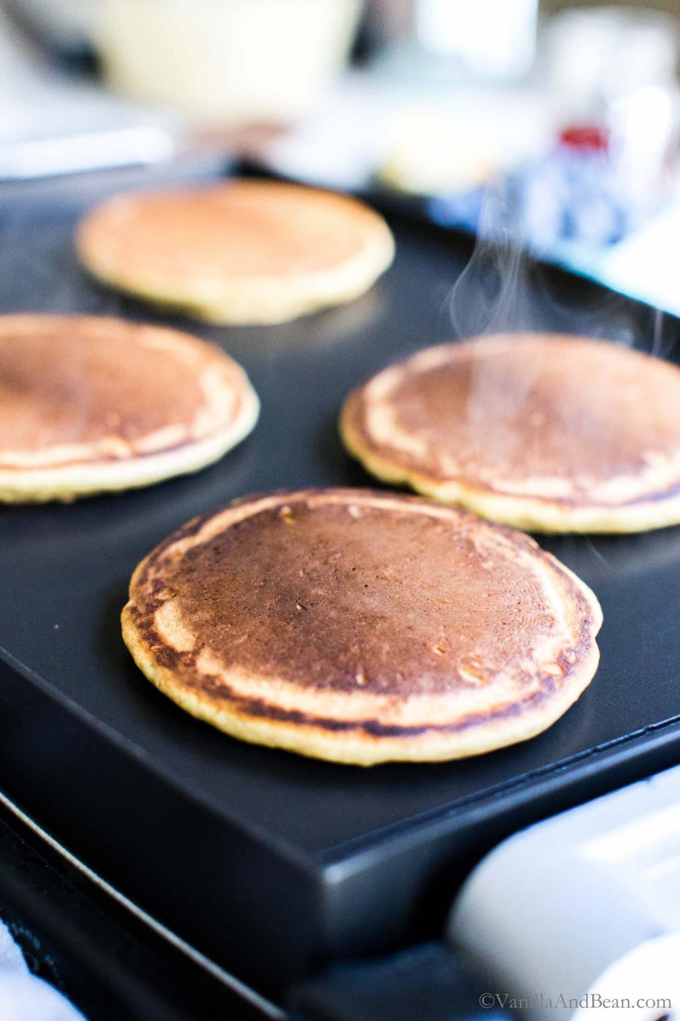 Sourdough pancakes on a griddle.