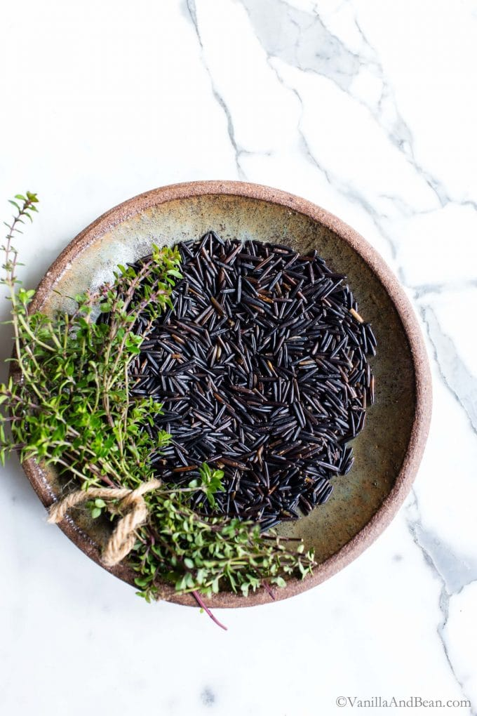 Wild rice in a bowl with thyme sprigs tied together on the side.