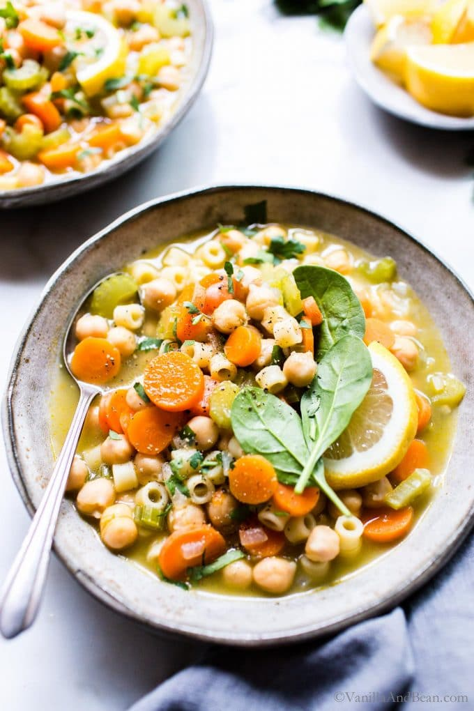 Vegetarian Noodle Soup with chickpeas in a bowl garnished with lemon and spinach.
