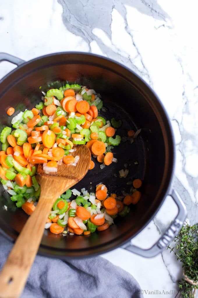 Carrots, onion and celery sauted in a Dutch oven making vegan chickpea noodle soup.