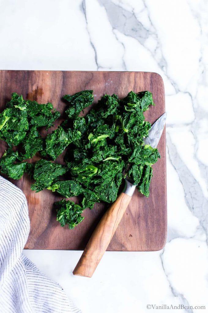 Chopping blanced kale on a cutting board.
