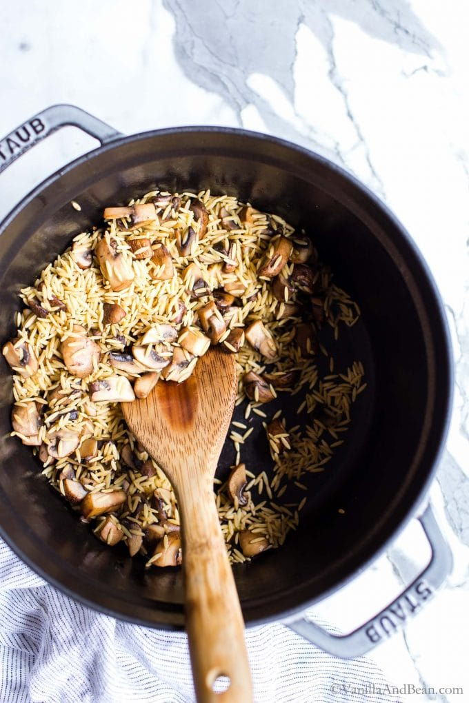 Mushrooms and orzo in a Dutch oven with a spoon.