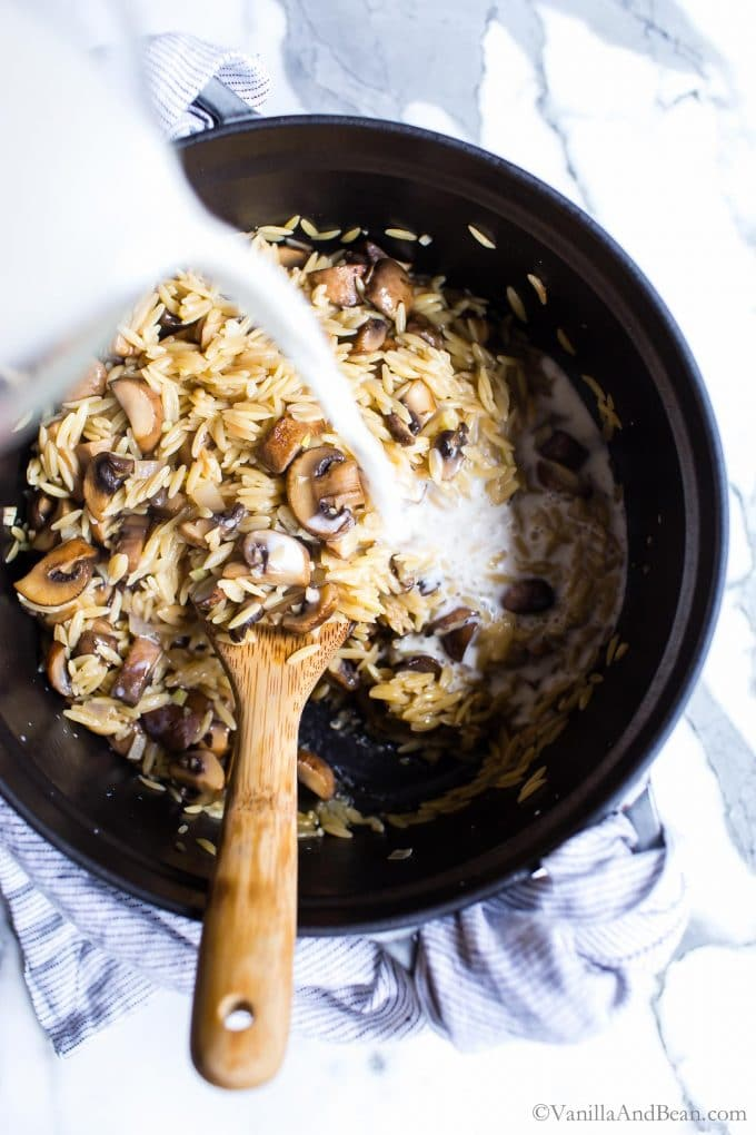 Milk being poured into a Dutch oven with orzo and mushrooms.