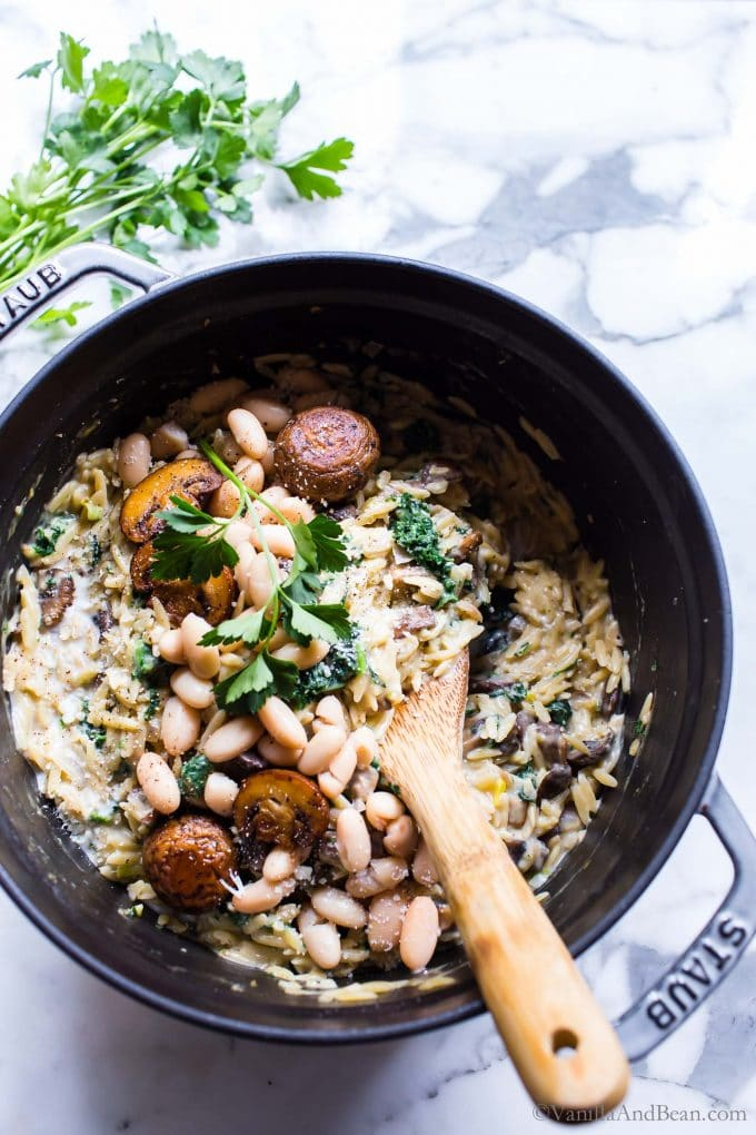 Creamy Orzo White Bean and Parmesan with Mushrooms in a Dutch oven garnished with parsley.