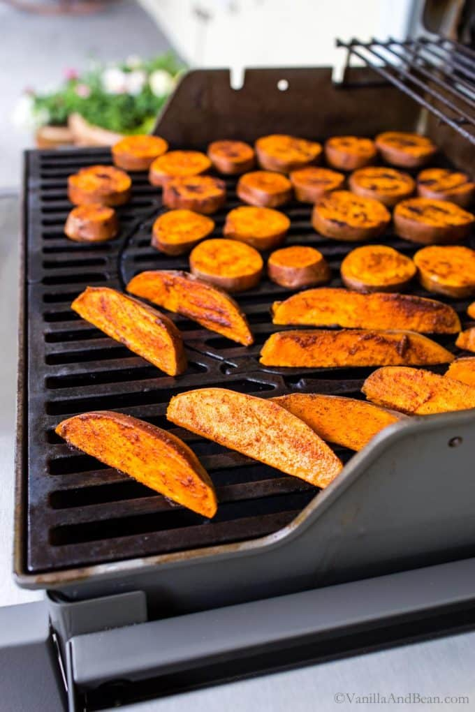 Grilled sweet potato slices and wedges on a gas grill.