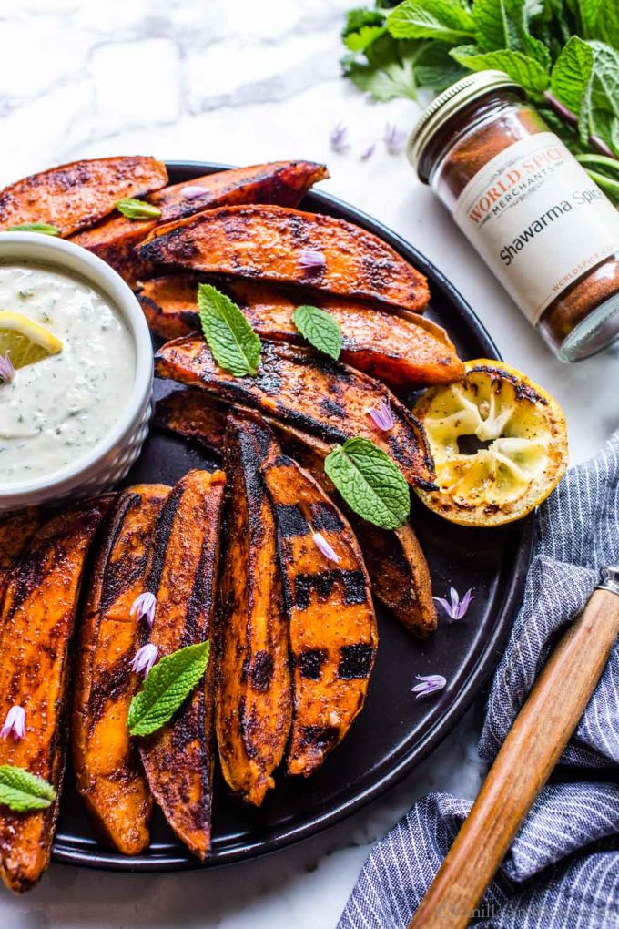 Grilled Sweet Potato Wedges on a plate with sauce and garnished with mint.