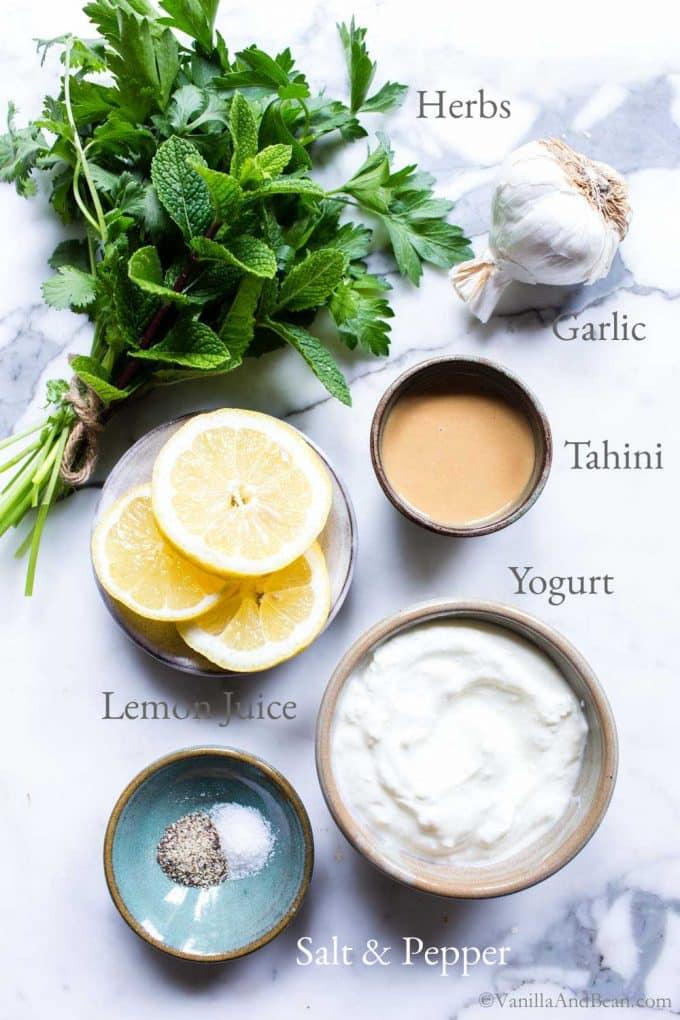 Yogurt tahini dip ingredients on a marble table.