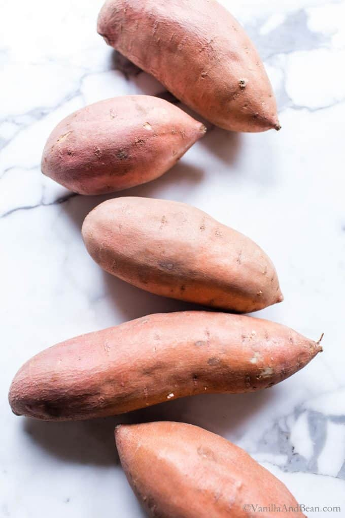 Whole Sweet Potatoes on a marble table.
