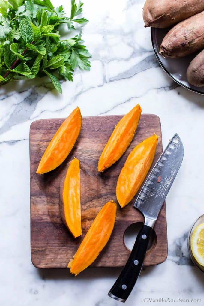 Sweet potato wedges on a cutting board.