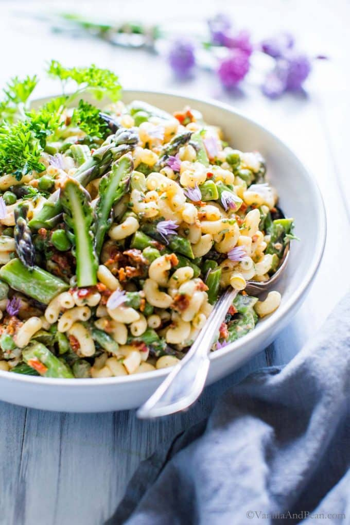 Dijon Asparagus and Pea Macaroni Salad in a bowl with a spoon ready for serving.