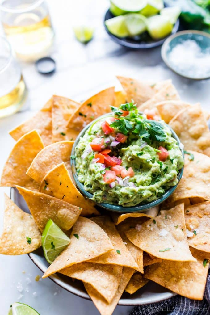 Creamy Guacamole Recipe in a bowl garnished with tomatoes and cilantro surrounded by tortilla chips.