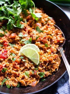 Mexican Rice Recipe Vegetarian in a pan, garnished with lime and cilantro.