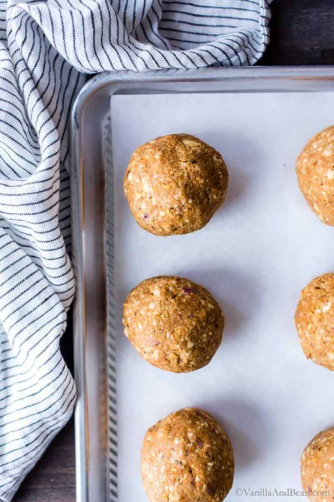 Chickpea burger raw ingredients rolled into balls on a parchment lined sheet pan.