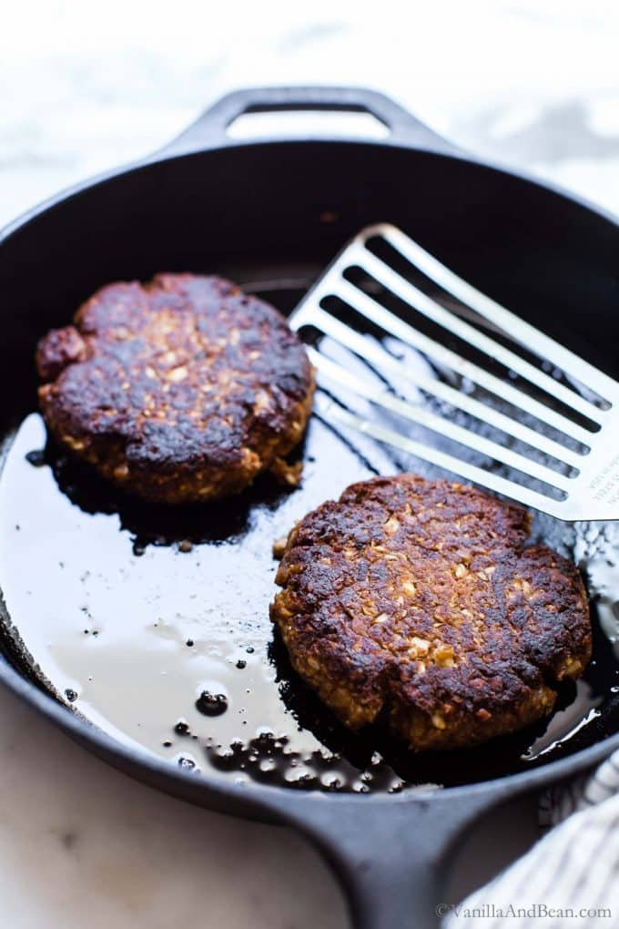 Pan fried chickpea patties in a cast iron skillet.