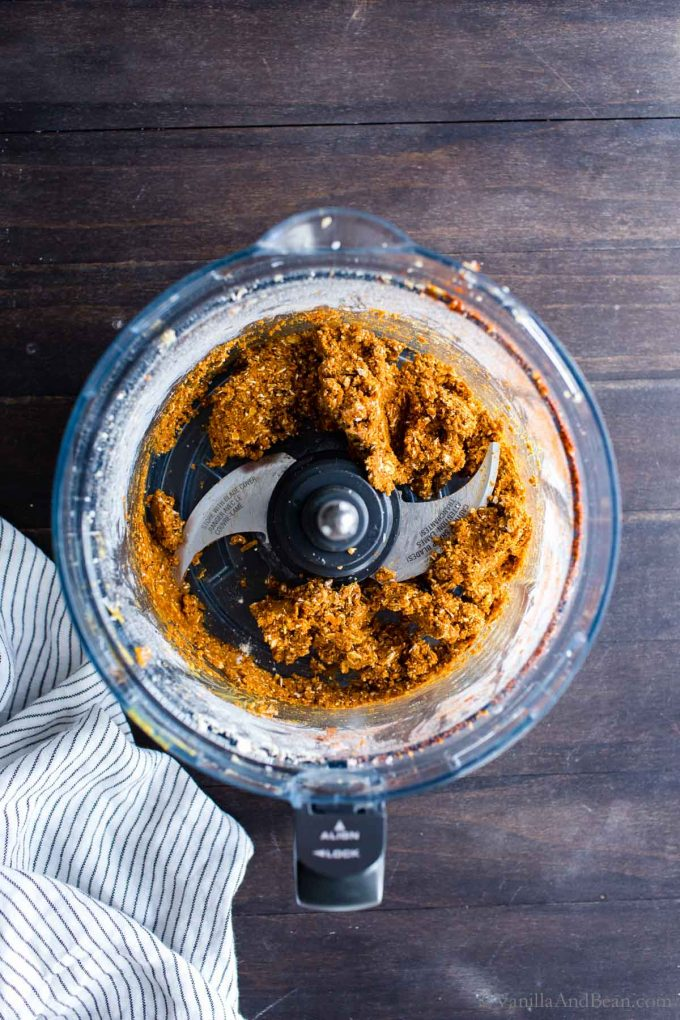 Spices and oat flour in the work bowl of a food processor, post processing.