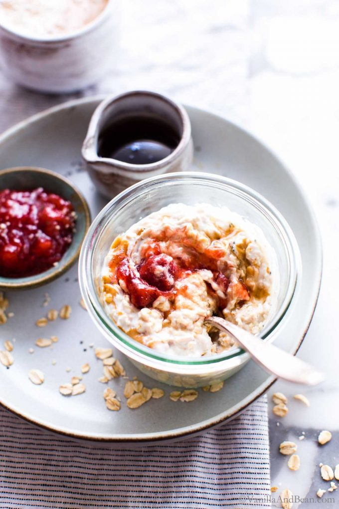 Overnight oats with peanut butter and jam in a glass jar with a spoon in it.