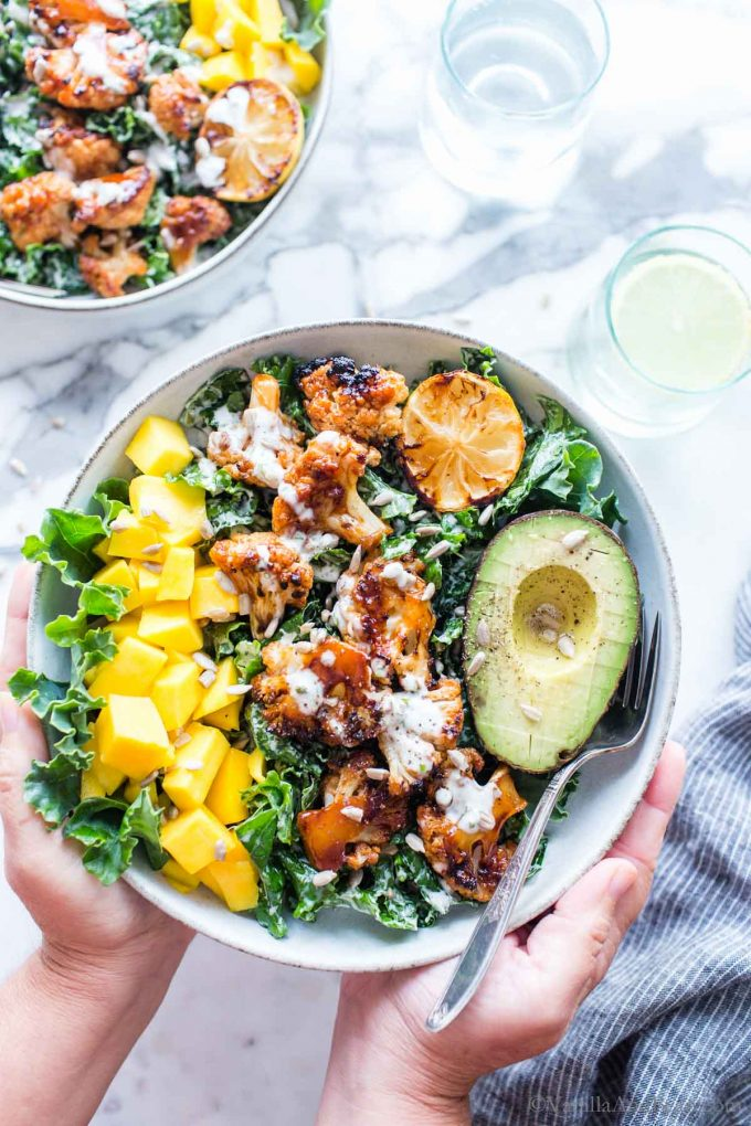 Hands holding a bowl of barbeque cauliflower florets with mango and avocado, garnished with sunflower seeds.