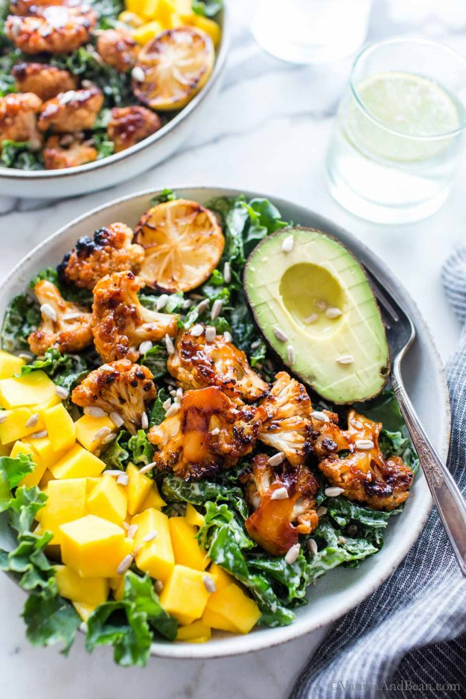 Grilled Barbecue Cauliflower Bowl with mango and avocado, garnished with sunflower seeds.