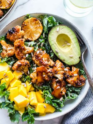 Grilled BBQ Cauliflower Bowl with mango and avocado, slathered with BBQ sauce and garnished with sunflower seeds.
