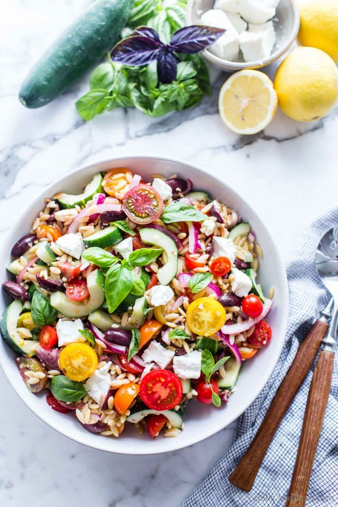 Greek orzo Salad in a large bowl with two serving spoons on the side.