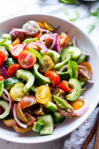 Cucumber Salad with Tomatoes and Onion in a bowl ready to share.