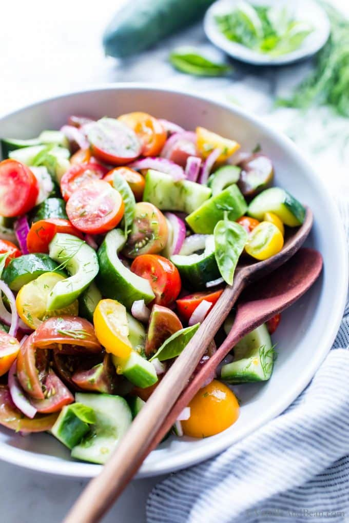 Close up of Cucumber Onion Tomato Salad with two spoons in the bowl.