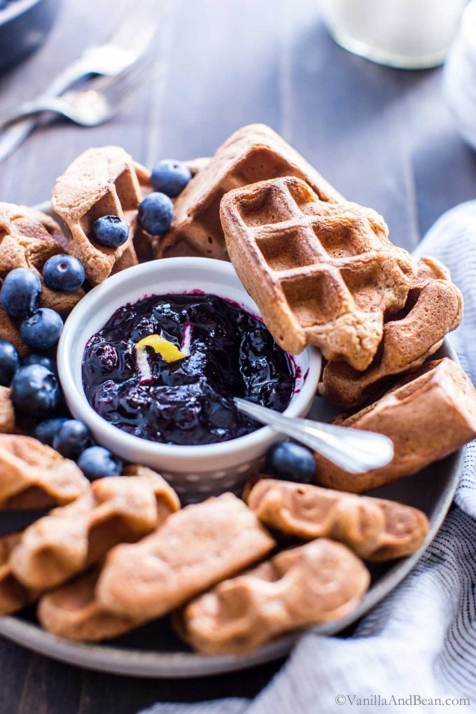 Blueberry Compote in a small serving dish surrounded by waffles.