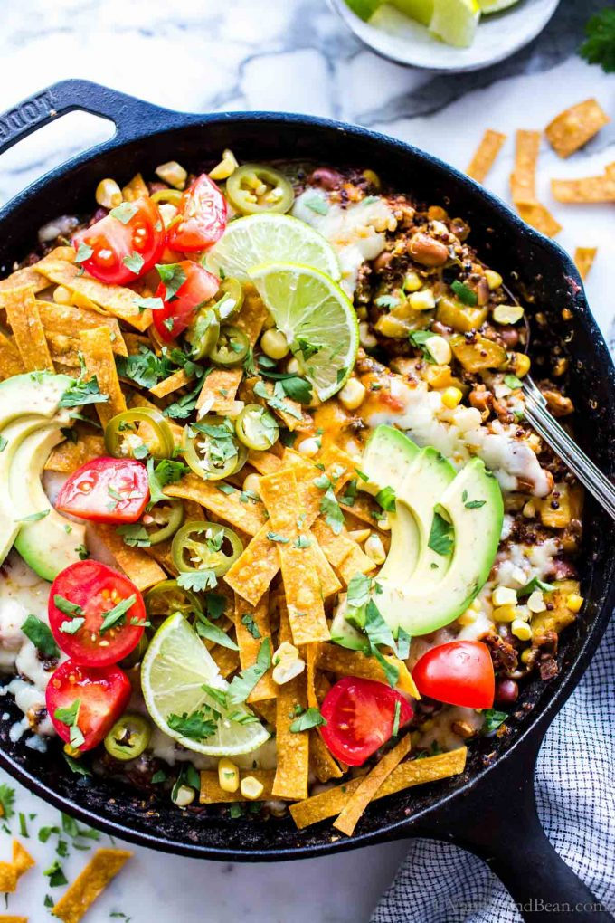 One Pan Mexican Quinoa Recipe Vegetarian in a skillet garnished with jalapenos and avocados.